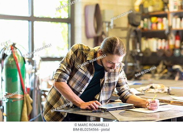 Caucasian man using digital tablet in workshop
