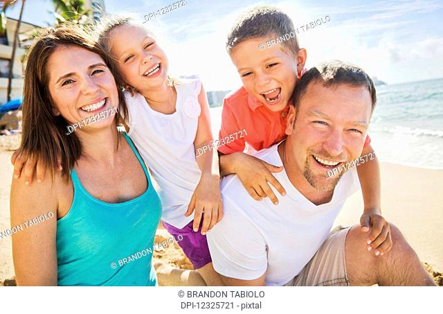Portrait of a family of four enjoying a summer vacation in Waikiki Beach; Honolulu, Oahu, Hawaii, United States of America