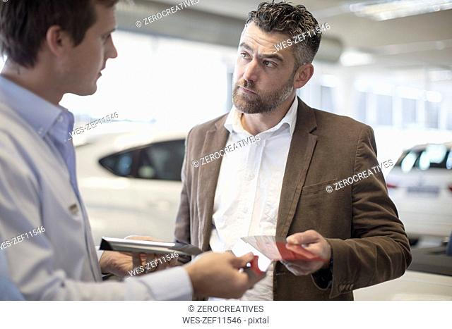Car dealer handing over color sample to client in showroom