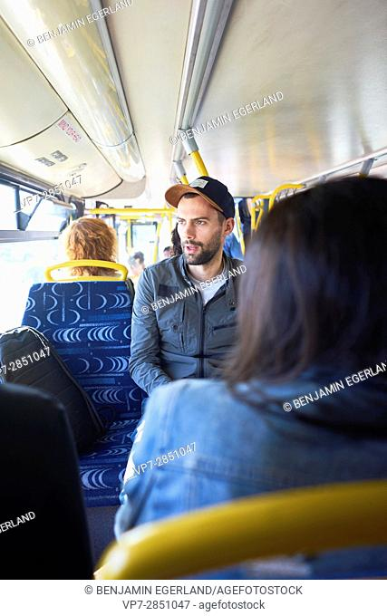 Young man with cap speaking with friends while sitting in public transport in Malta, Europe