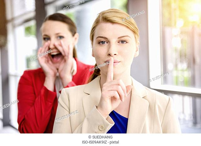 Businesswomen hiding and letting out secret