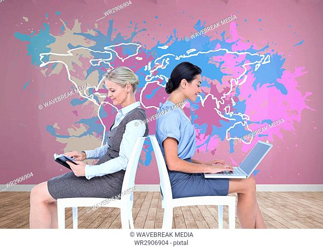 Businesswomen collaborating working in front of Colorful Map with paint splattered wall background
