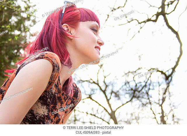 Portrait of smiling young woman with pink hair