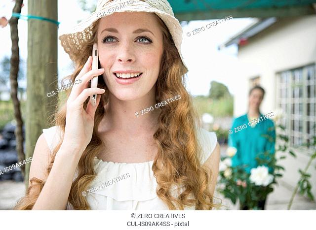 Young woman chatting on smartphone in rose garden centre