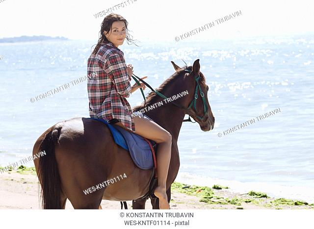 Indonesia, Bali, Woman riding a horse at beach