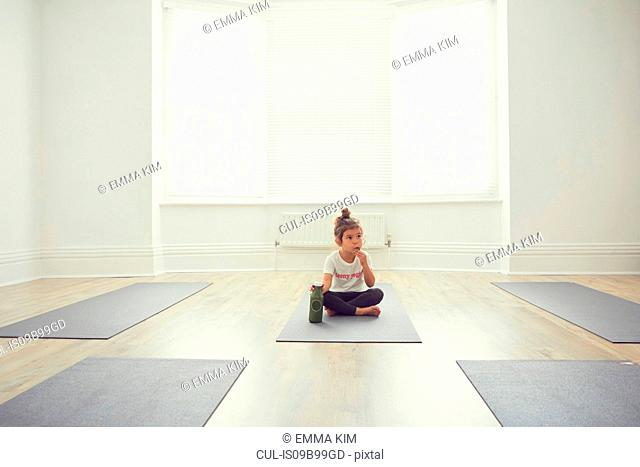 Young girl in yoga studio, sitting on yoga mat
