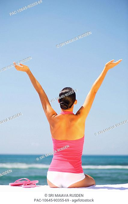 Hawaii, Oahu, Attractive young woman in bright colors sits by turquoise ocean, arms raised inthe air