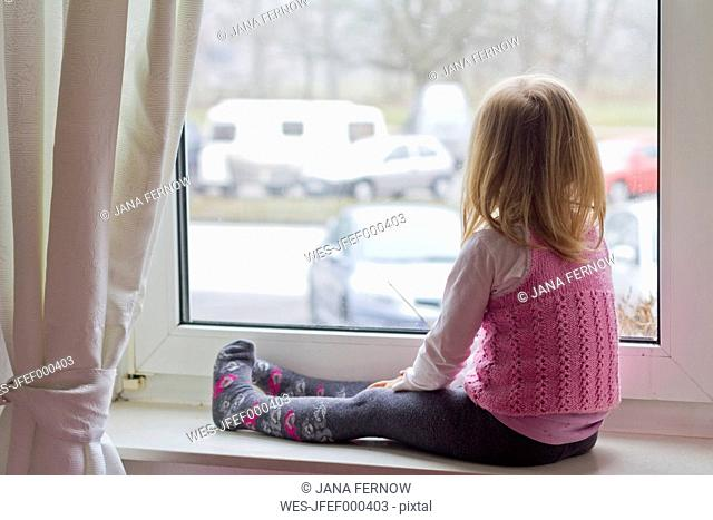 Little girl sitting on window sill looking out of window