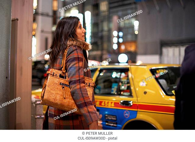 Side view of mature woman carrying handbag on shoulder waiting to cross road, Ginza, Tokyo, Japan