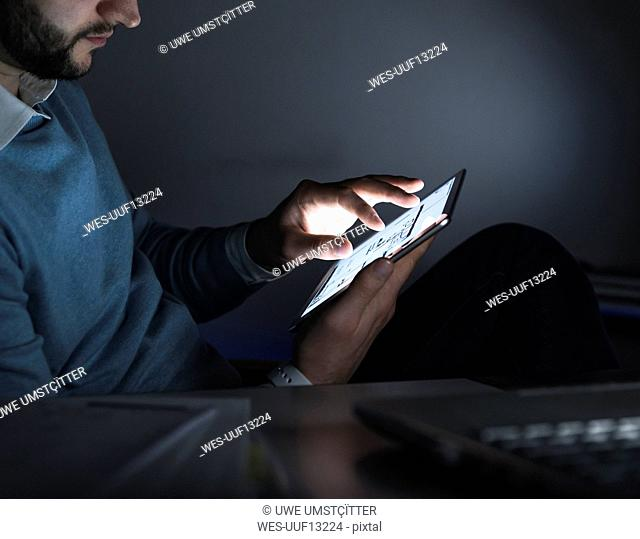 Businessman working on tablet in office at night, close-up