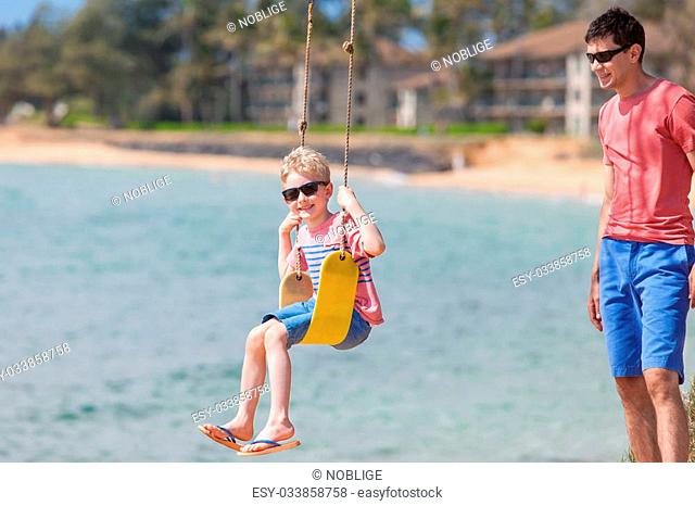 family of two having fun swinging at tropical beach enjoying summer vacation