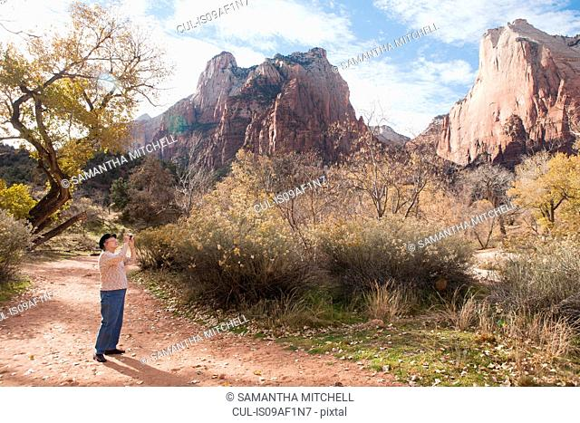 Senior woman photographing view in Zion National Park, Utah, USA