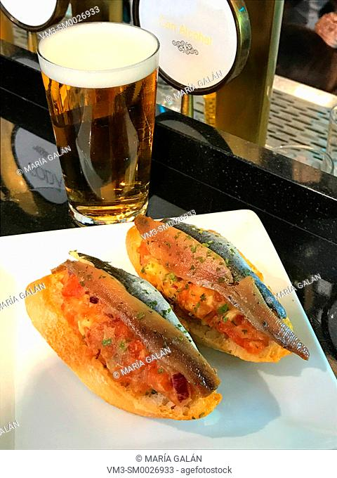 Spanish tapa: anchovy fillets with tomato sauce on toast and glass of beer. Spain