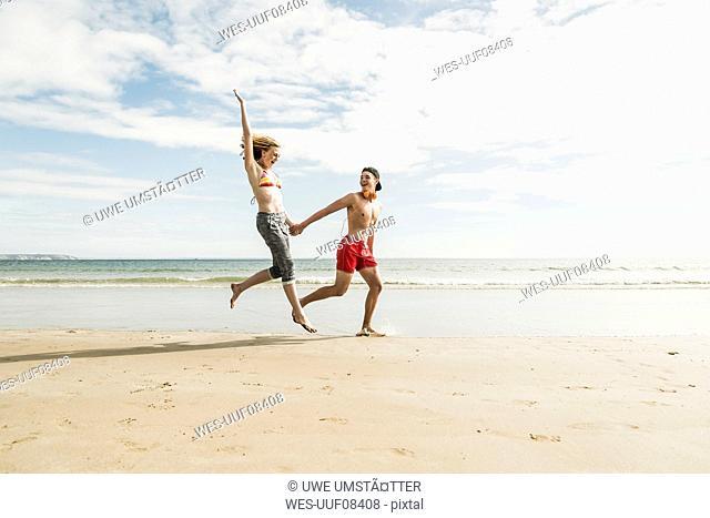 Happy teenage couple on the beach