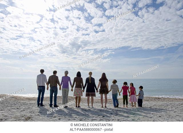Group of people standing on beach, holding hands