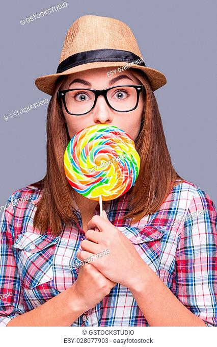 Sweet and colorful. Beautiful young woman holding lollipop in front of her mouth while standing against grey background