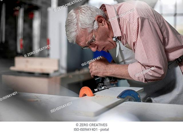 Senior carpenter using jigsaw tool in workshop