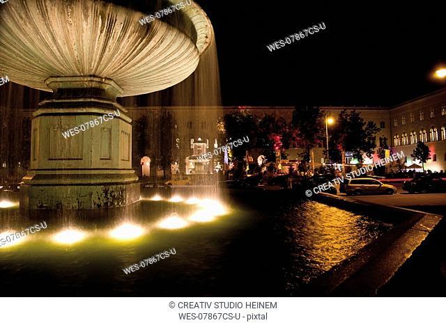 Germany, Bavaria, Munich, Illuminated fountain in front of University