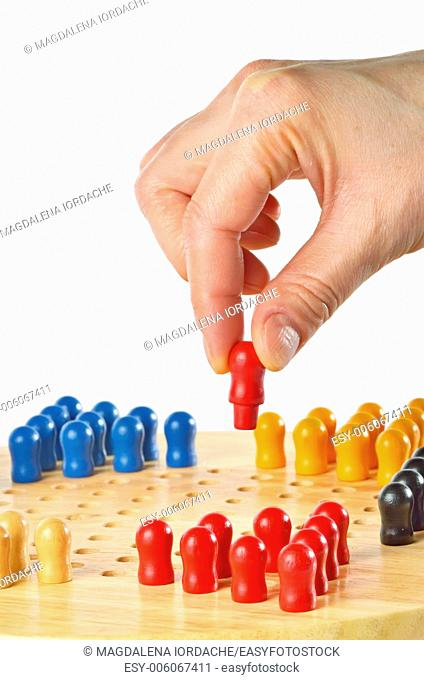 woman hand playing a game of Chinese checkers. Isolated on white
