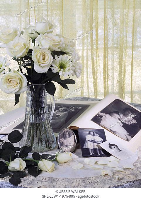 white roses in glass vase, old photos, lace cloth