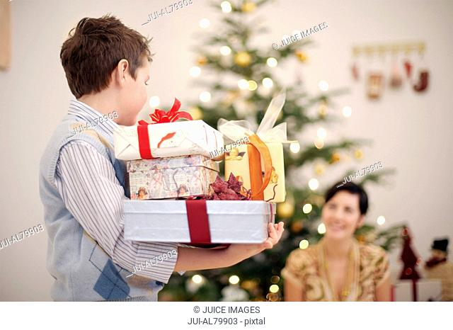 Boy carrying stack of Christmas gifts