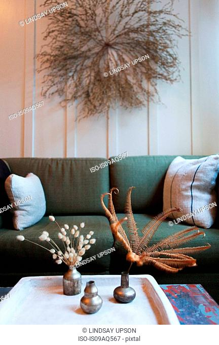 Sitting room with dried flower arrangements on wall and coffee table