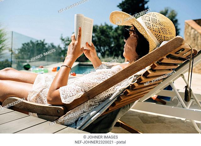 Woman reading on sunchair