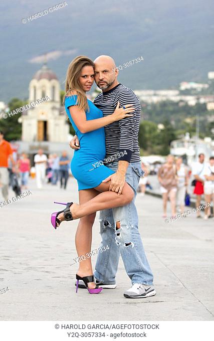 Couple of lovers having fun and taking photographs themselves with remote control on the promenade of Yalta, Crimea
