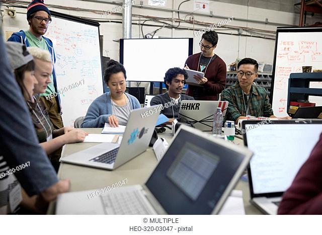 Hackers working hackathon at laptops in workshop