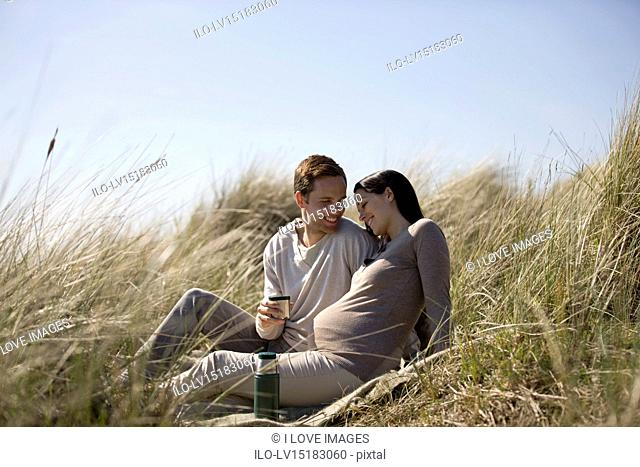 A pregnant woman and her partner sitting amongst the sand dunes, sharing a hot drink