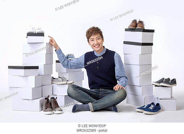Young smiling man sitting down with stacked boxes of sneakers