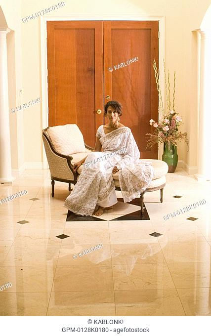 Portrait of mature woman dressed in sari sitting on chair in foyer, looking at camera