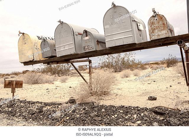 Row of mailboxes on shelf, California, USA