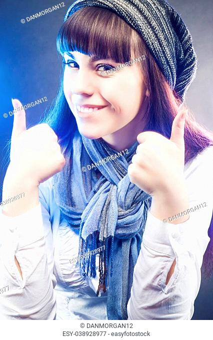 portrait of Smiling and Happy Caucasian Girl in Winter Long Hat Showing Thumbs Up in Studio Environment. Vertical Image