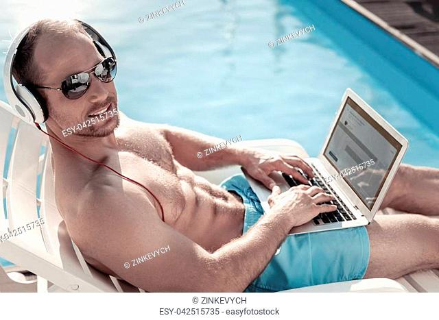Loving my job. Well built entrepreneur looking into the camera with a cheerful smile on his face while working outdoors and sunbathing alone