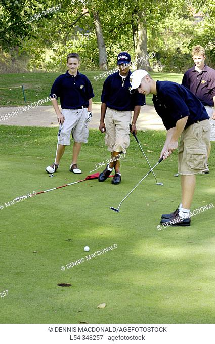 High school students makes a putt during a golf tournament