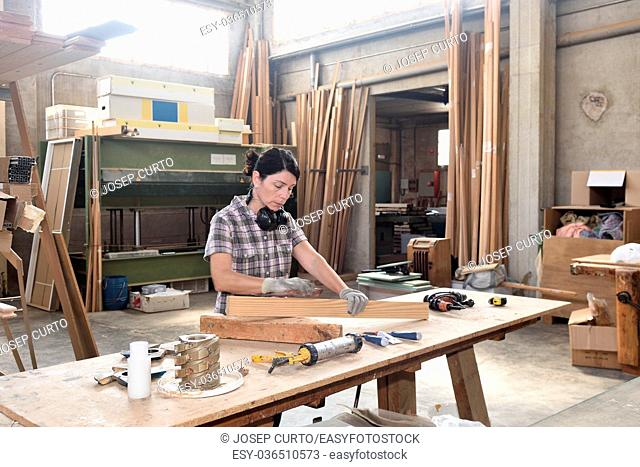a woman working in a carpentry workshop,sand