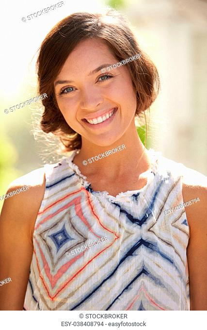 Outdoor Portrait Of Attractive Young Woman Smiling At Camera