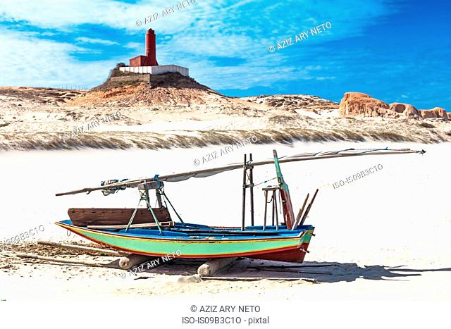 Beached fishing boat and lighthouse, Fortim, Ceara, Brazil