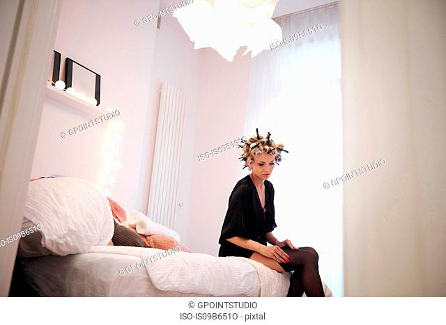 Woman with hair rollers sitting on bed putting on stocking