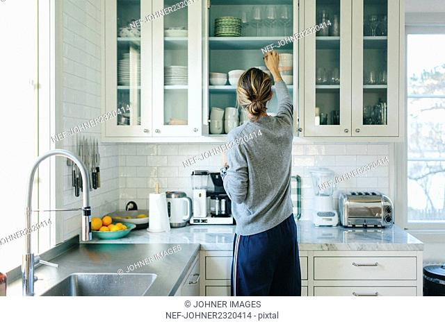 Woman reaching for bowl from kitchen cupboard