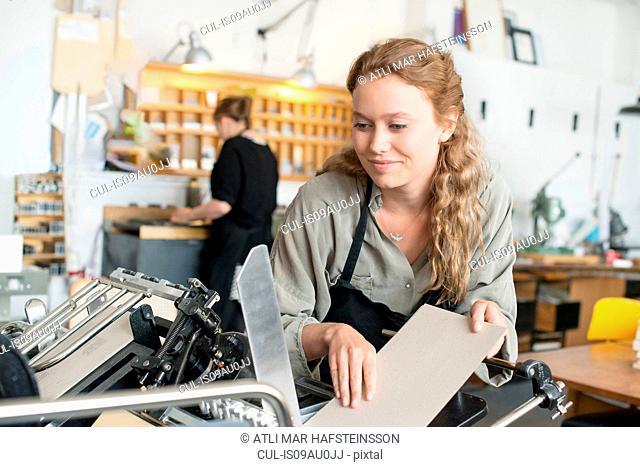 Female printer inserting paper to machine in workshop