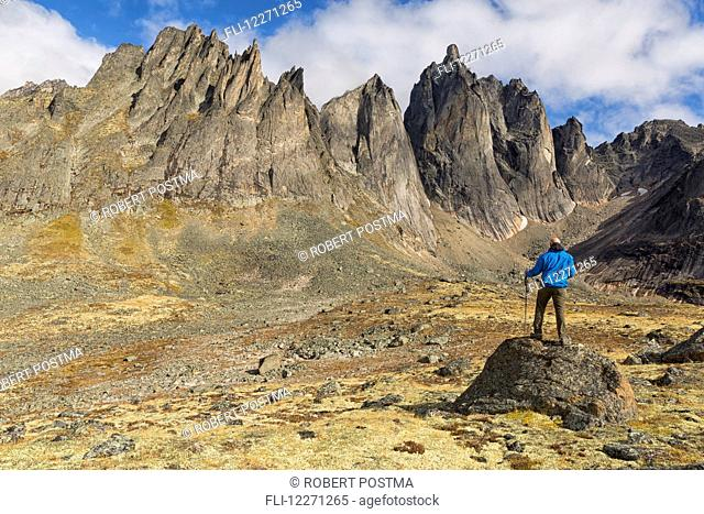 Man standing on a rock overlooking the jagged granite peaks of Tombstone Territorial Park; Yukon, Canada