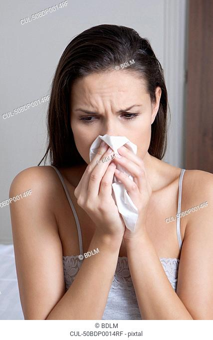 Woman blowing her nose on bed