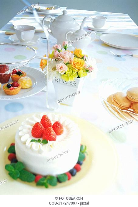 Strawberry cake and dishes on dining table