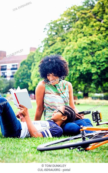 Boy and mother relaxing and reading in park
