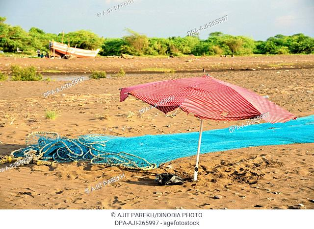 Umbrella and fishing net, Surwada Beach, Gujarat, India, Asia