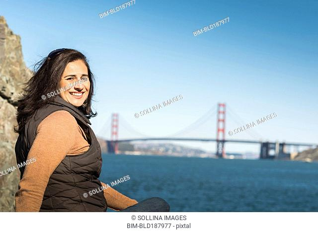Mixed race woman smiling near Golden Gate Bridge view, San Francisco, California, United States