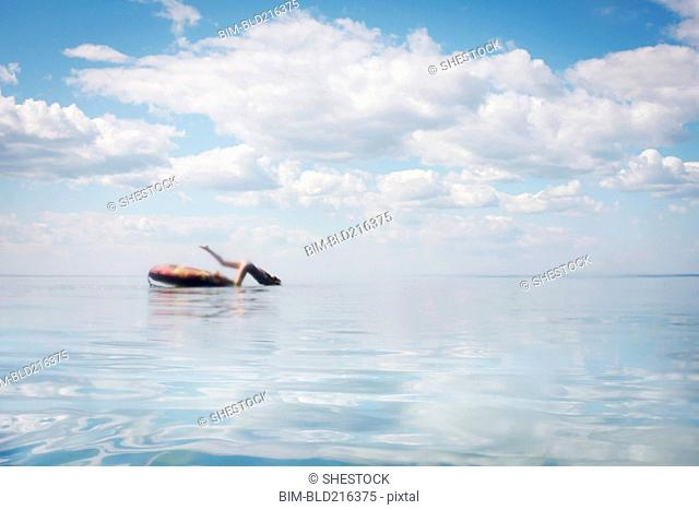 Caucasian teenage girl jumping from inner tube into lake