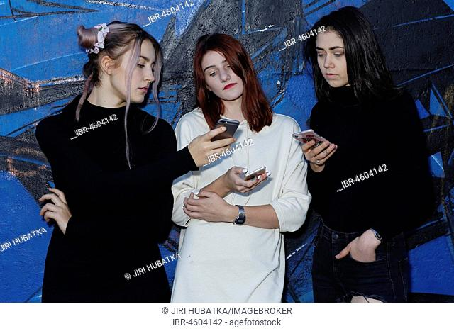 Three girls, teenagers, with mobile phones, puberty